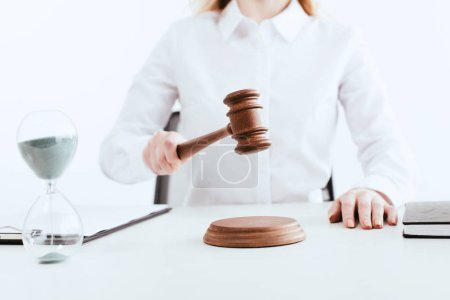 selective focus of female judge with gavel in hand near hourglass with running sand isolated on white