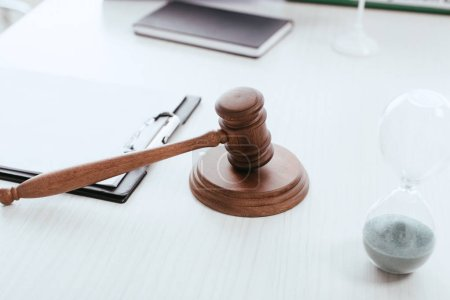 selective focus of wooden gavel near objects on table