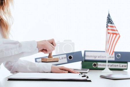 cropped view  of female lawyer with stamp in hand isolated on white