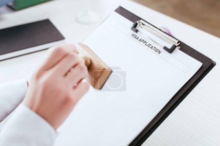 Photo pour Focus sélectif du presse-papiers avec lettrage de la demande de visa sur le document en main de l'avocate - image libre de droit