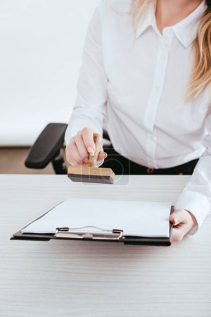 selective focus of  female lawyer holding clipboard and stamp in hands