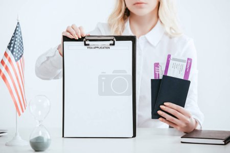cropped view of woman holding passports with tickets and clipboard with empty blank with visa application lettering