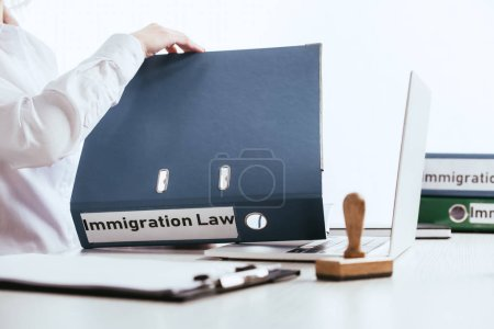 selective focus of woman opening folder with immigration law lettering near laptop isolated on white