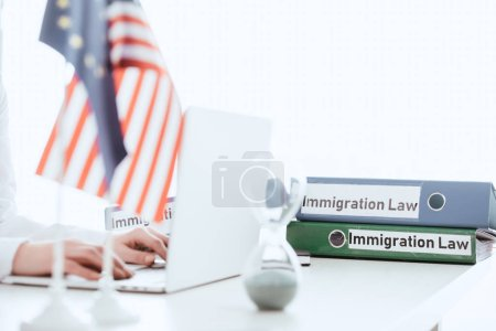 selective focus of woman typing on laptop near hourglass and american flag
