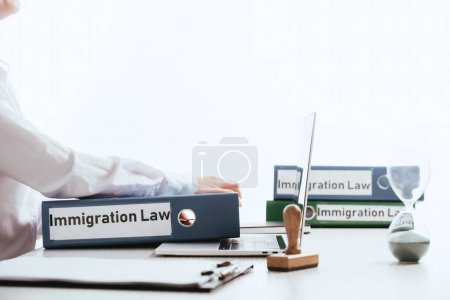 selective focus of woman taking folder with immigration law lettering near laptop isolated on white