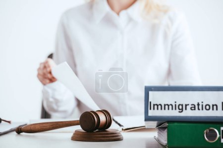 selective focus of gavel near folders with immigration law lettering with woman on background isolated on white