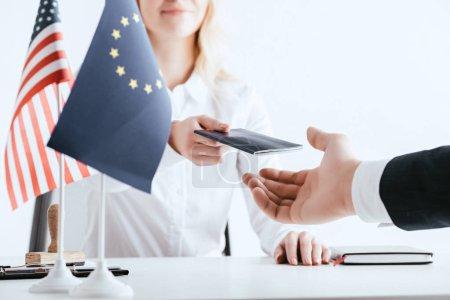 Foto de Vista recortada de la mujer dando pasaporte a turistas cerca de banderas americanas y europeas, aislado en blanco - Imagen libre de derechos