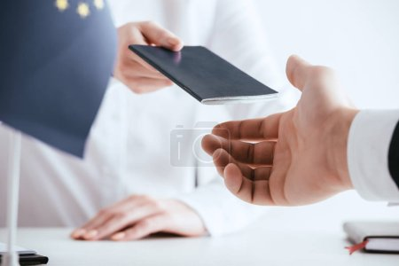 cropped view of travel agent giving passport to tourist isolated on white