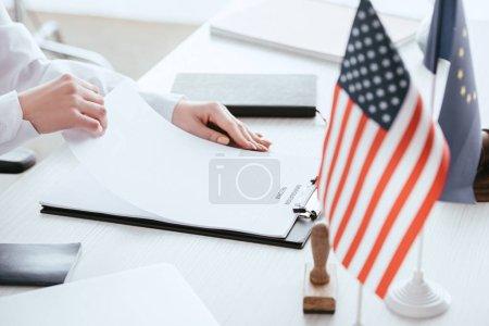 Photo pour Vue recadrée de femme tenant le document avec le lettrage de réforme de l'immigration près des drapeaux américains et européens - image libre de droit