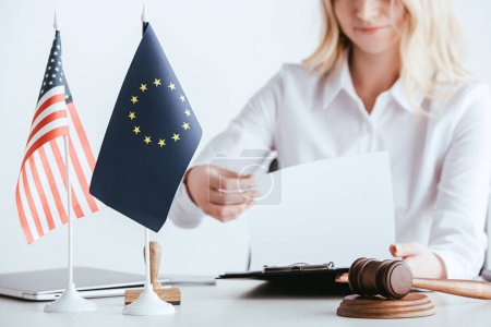Photo for Cropped view of woman holding document near american and european flags isolated on white - Royalty Free Image