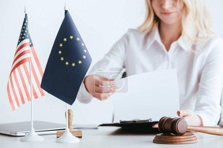 Photo pour Vue recadrée de femme tenant le document près des drapeaux américains et européens isolé sur blanc - image libre de droit