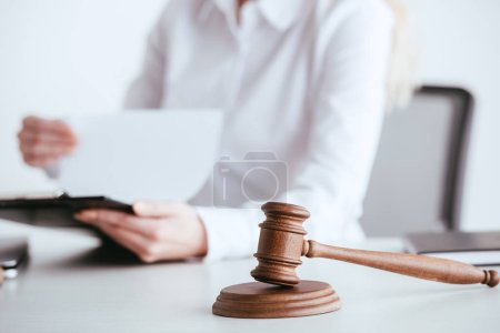 Photo for Selective focus of gavel near woman holding clipboard with document on background isolated on white - Royalty Free Image