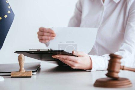 Photo pour Foyer sélectif de la femme tenant presse-papiers avec document près du marteau isolé sur blanc - image libre de droit