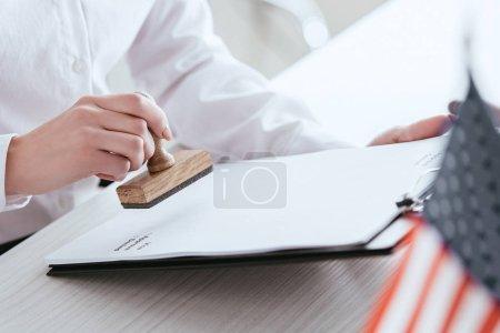 Photo pour Foyer sélectif de la femme apposant son timbre sur le document - image libre de droit