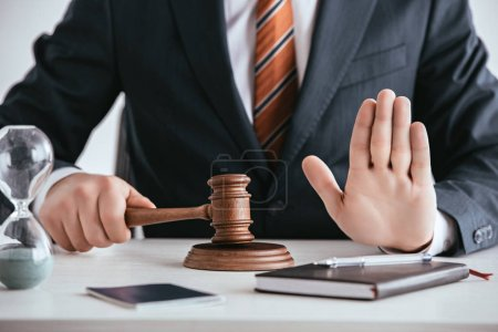 Photo for Cropped view of judge in suit holding gavel and showing stop sign - Royalty Free Image