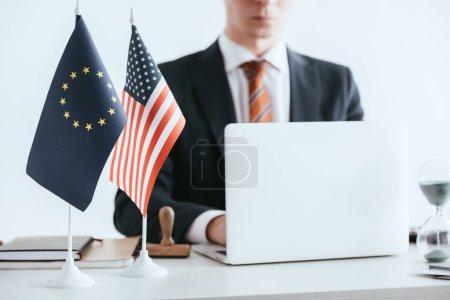 Photo pour Foyer sélectif de l'ordinateur portable et des drapeaux internationaux avec l'homme utilisant l'ordinateur portable sur fond isolé sur blanc - image libre de droit