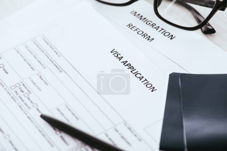 selective focus documents with lettering near glasses and passports