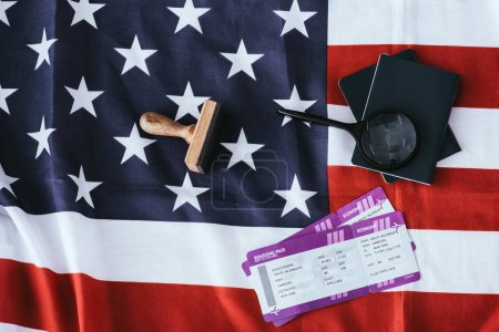 top view of passports and magnifier near tickets and american flag