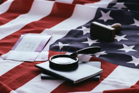 selective focus of passports and magnifier near tickets and american flag