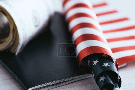 close up of american flag near passport and dollar banknotes