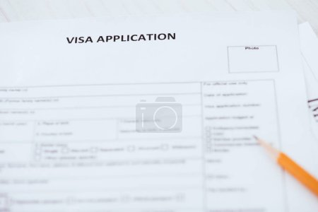 selective focus of visa application lettering on document near wooden pencil