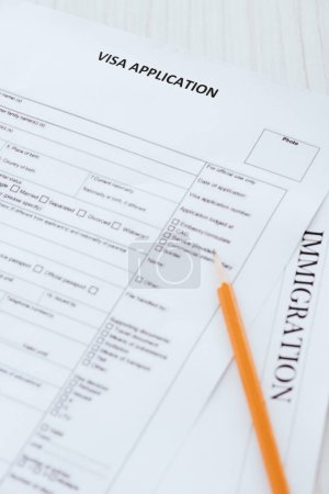pencil near documents with visa application and immigration lettering