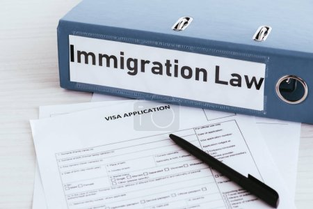 selective focus of folder with immigration law lettering near documents