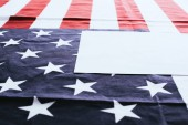 selective focus of american flag with stars and stripes near blank with copy space