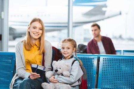 Photo pour Foyer sélectif de la mère détenant des passeports avec des billets d'avion et souriant près de la fille à l'aéroport dans le salon de départ - image libre de droit