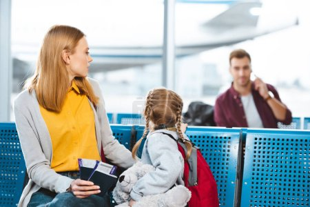 Photo for Selective focus of mother holding passports with air tickets near daughter and looking at man in airport - Royalty Free Image