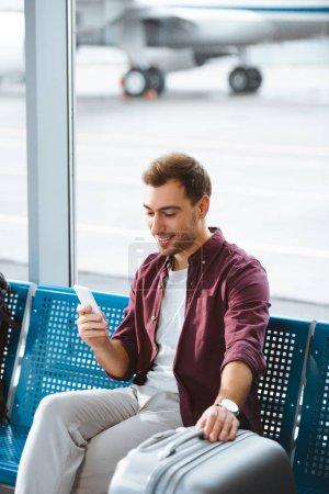 Photo pour Gai homme regardant smartphone et souriant tout en maintenant des bagages à l'aéroport - image libre de droit