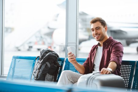 cheerful man looking at camera while holding smartphone and luggage in departure lounge