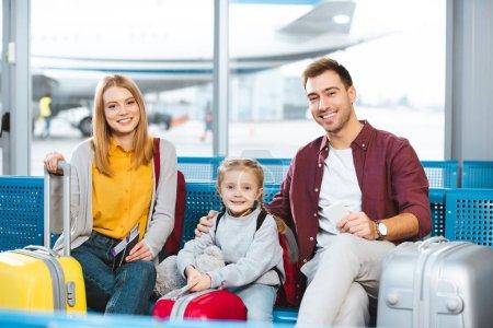 Photo pour Heureux famille assis dans le salon de départ et souriant près des bagages à l'aéroport - image libre de droit