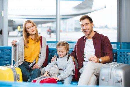 Foto de Feliz familia espera en sala de embarque y sonriendo cerca de equipaje - Imagen libre de derechos
