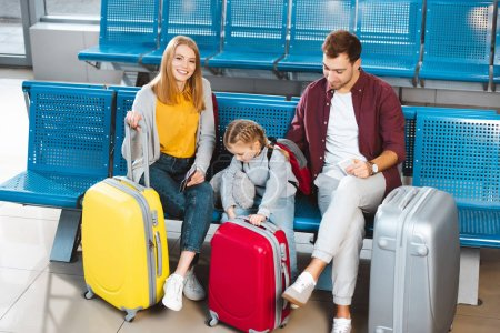 happy family sitting near luggage and smiling while waiting for flight in airport