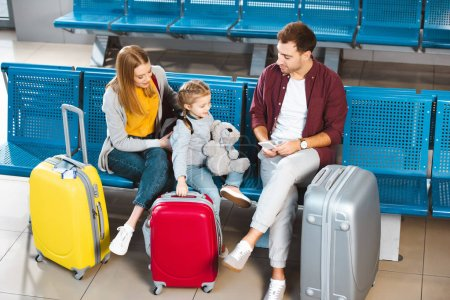 overhead view of father looking at daughter near suitcases and wife in departure lounge