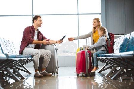 Photo pour Beau père donnant des passeports avec des billets d'avion à la femme près de la fille à l'aéroport - image libre de droit