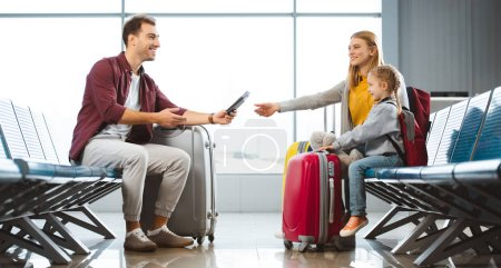 smiling father giving passports with air tickets to wife near daughter in airport