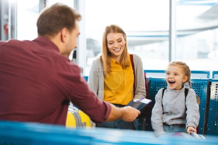 selective focus of father giving passports with air tickets near wife and daughter in airport