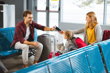 happy wife sitting with daughter and  giving passports with air tickets to husband in airport