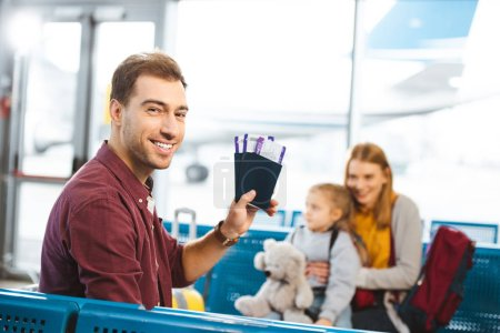 Photo for Selective focus of handsome man smiling while holding passports with air tickets with wife and daughter on background - Royalty Free Image