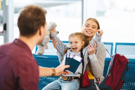 Photo for Selective focus of cheerful daughter holding hands above head and smiling with mother near father with passports with tickets - Royalty Free Image