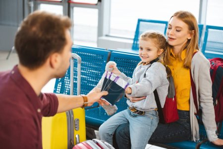 selective focus of cute daughter looking at dad with passports and air tickets while sitting with mom in departure lounge