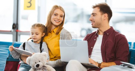 happy wife and husband smiling near daughter with digital tablet in departure lounge