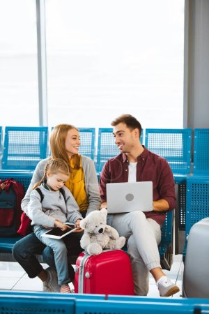 happy wife and husband looking at each other near daughter using digital tablet in waiting hall