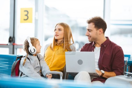 cute kid in headphones looking at mother while sitting near father in airport