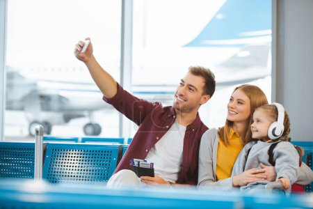 happy family taking selfie and smiling in departure lounge
