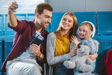 cheerful dad holding passports with air tickets and taking selfie with smiling wife and daughter in airport