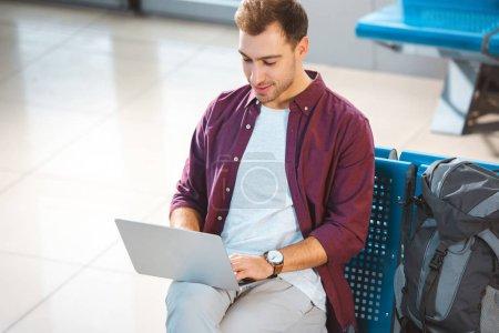 Photo pour Vue aérienne de l'homme gai, utilisant l'ordinateur portable assis dans la salle d'embarquement - image libre de droit