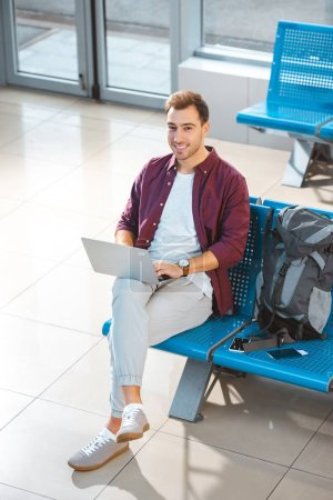 overhead view of smiling man using laptop while waiting in departure lounge